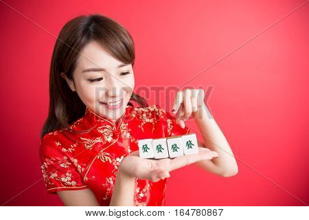 beauty woman wear cheongsam and show mahjong to you in chinese new year - Rich and wealthy text on girl hand in Chinese words