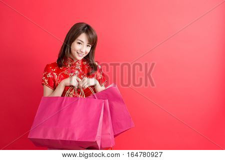 beauty woman wear cheongsam and take shopping bag in chinese new year