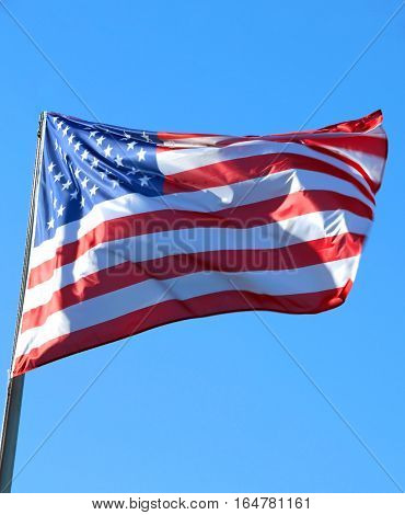 Large American Flag Flying High In The Blue Sky