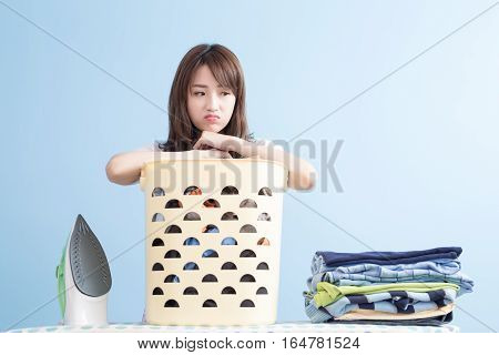 beauty housewife feel sad with ironing and shirt isolated on blue background