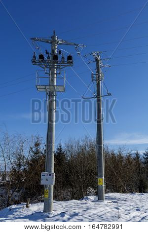 Connection between two new electric power pole connect to the high voltage electric wires on blue sky background. Potential transformer and current transformer on concrete power pole.