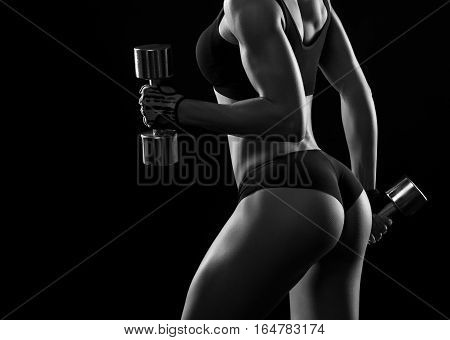 Every muscle put to work. Black and white cropped closeup of a fit sportswoman in exercising clothes pumping iron showing off her perfect buttocks