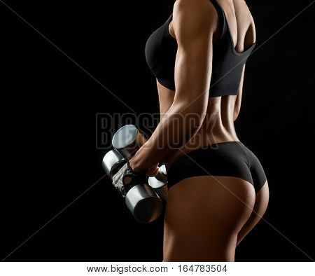 Look of the healthy lifestyle. Cropped shot of a sporty muscular fit woman in sportswear posing with dumbbells in her hands against black background