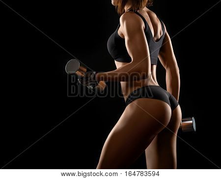 Make those biceps burn Cropped studio shot of a toned strong fitness woman pumping iron doing exercises on her biceps against black background