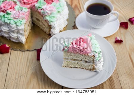 piece of sponge cake  with curd cream  and banana on  background of cake and cup of coffee