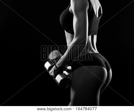 Limitless lifestyle. Black and white shot of a hot and sexy female with athletic toned body holding weights copyspace on the side
