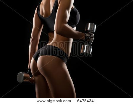 Shaping her arms. Cropped shot of a fitness woman doing biceps exercises with dumbbells against black background