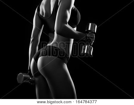 Challenging goals. Cropped monochrome shot of an attractive female bodybuilder in sports top and shorts posing with dumbbells at studio
