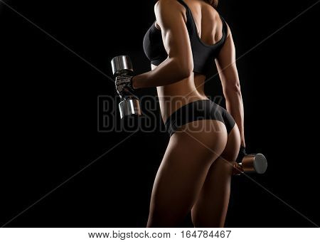 Pump it up. Shot of a young fitness woman with gorgeous body working out with dumbbells