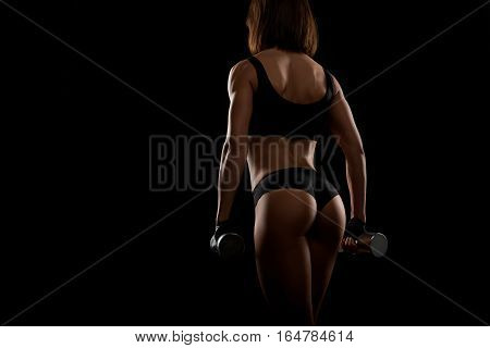 Serious about her looks. Horizontal rearview shot of a sporty woman in exercising outfit working out with weights copyspace on the side