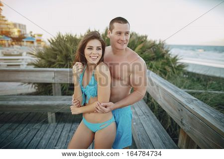 young sporty couple walking on the beach and posing for the photographer
