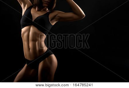Hard work pays off. Cropped horizontal shot of a stunning fitness lady with perfectly shaped abs against black background copyspace on the side