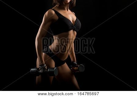 Six pack in sight. Horizontal studio shot of a fitness woman with strong muscular body working out with dumbbells copyspace