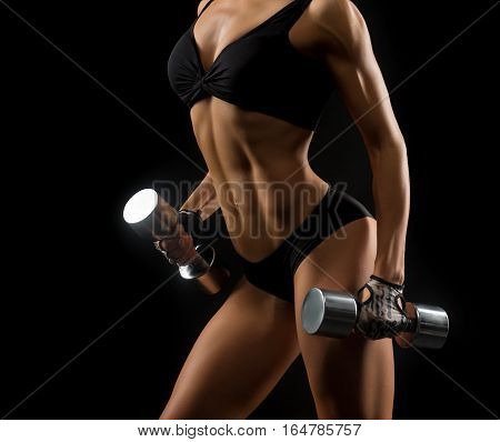 Committed to sport. Cropped studio closeup of a stunning fitness woman with hot sexy body holding dumbbells on black background