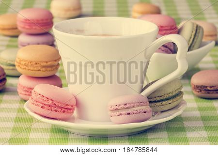 Cup of black coffee with sweet colorful French macaroon biscuits