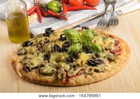 freshly baked pizza with olive basil and melted cheese on a wooden board