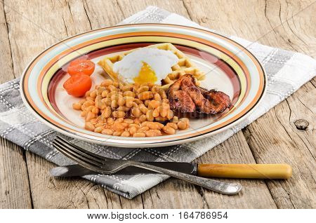 scottish breakfast with baked beans fried bacon tomatoes waffle with poached egg on a plate