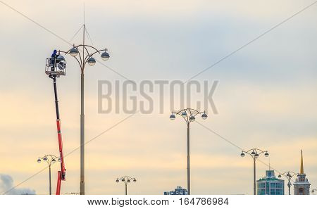 Electricians repairing street lights in the winter evening in city
