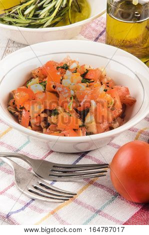 fresh tomato salad with parsley and crushed black peppercorn in a white bowl