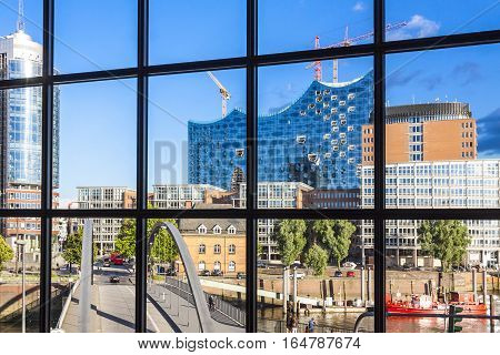 HAMBURG GERMANY - JUNE 25 2014: The Elbphilharmonie concert hall in the port of Hamburg. The tallest inhabited building of Hamburg with a height of 110 metres. View through the window