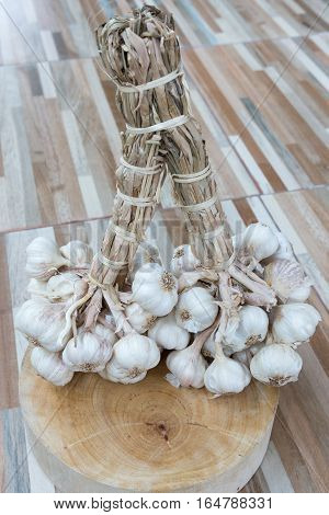 Fresh garlic bunch on the wooden chopping block for cooking the Thai food.