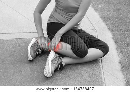 Sporty woman ankle sprain while jogging or running at park - black and white concept