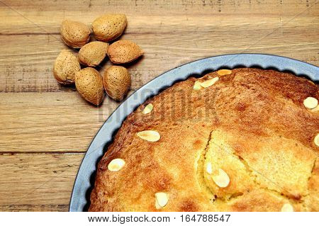 Unshelled Almond Nuts Next To A Freshly Baked Frangipane Tart Or Cake