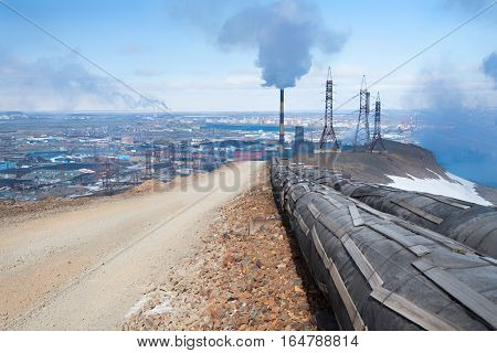 Mountain gravel road. The wide road leads to the smelter. Industrial landscape.