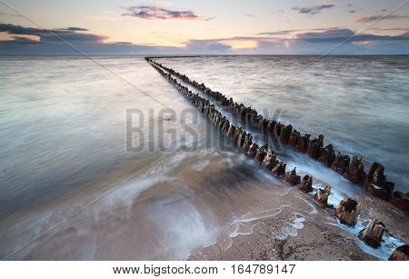 old breakwater in sea waves at sunset Netherlands