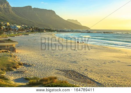 Popular Camps Bay Beach with its white beach, attracts a large number of foreign visitors and is an affluent suburb of Cape Town in Western Cape, South Africa. Shot taken at sunset.