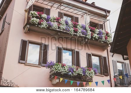 Classic town building at daytime. Bright flowers on balconies. New residential quarter.