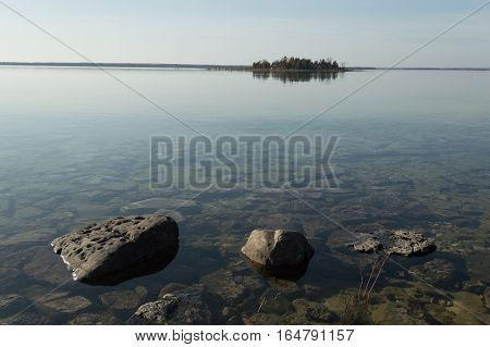 Dead calm afternoon image of shallow and clear lake huron water and limestone rocks along theshoreline. A small tree-covered island is on the horizon. Overall feeling is a calm peaceful tranquil serene and wild background.
