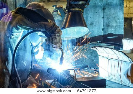 Working welder welds the parts at the factory. A process using a semi-automatic welding.