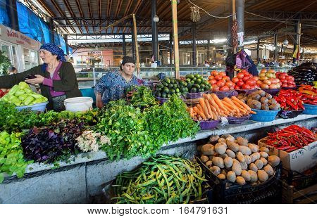 SIGNAGI, GEORGIA - OCT 3, 2016: Village woman selling fruits and vegetables inside market with fresh farmer's products on October 3, 2016. Signagi of Kakhetia has a population 2.200