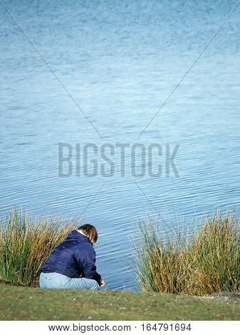 Homeless woman sitting by a lake outside feeling sad and rejected.