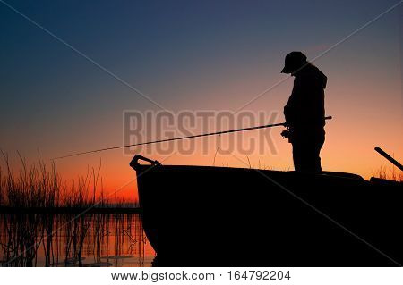 The picture shows a silhouette of a fisherman. Fisherman stands in the boat and catches a fish. Fishing rod is horizontal. Fisherman waiting when the fish bite.
