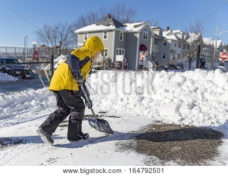 child cleans snow in the yard. boy shoveling snow. the concept of selfless assistance, citizen responsibility poster