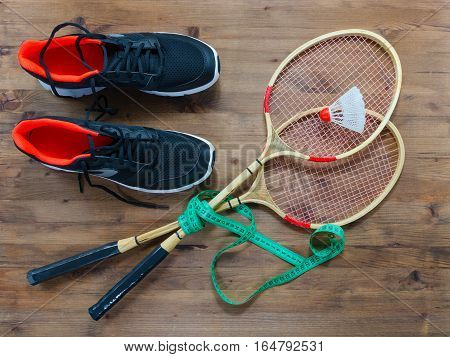 Shuttlecock and badminton racket with sport shoes on wooden background