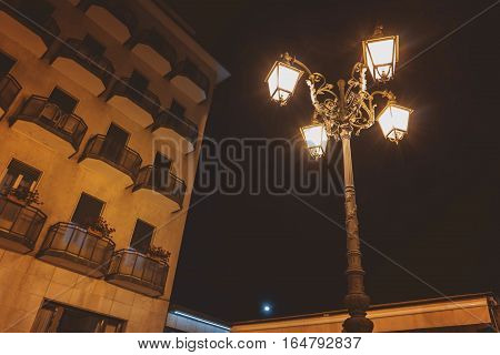 Street lamp at night. Town building and dark sky. Midnight in Stresa.