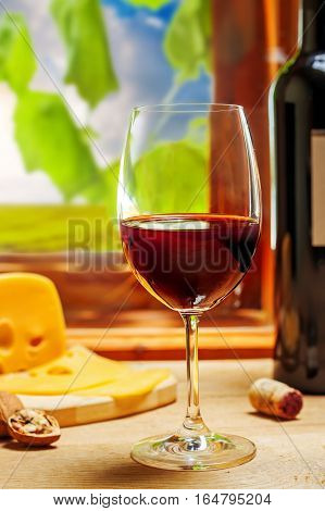 Glass of wine on table, vineyard landscaped on background.