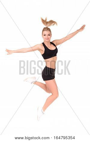 Beautiful active woman in a fitness wear jumping isolated over white background.