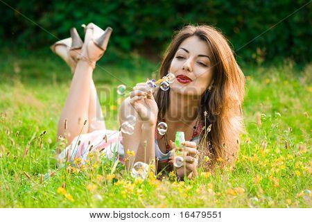 menina inflar bolhas de sabão no campo