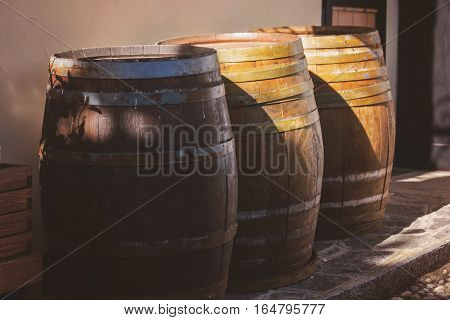 Old wooden barrels outdoor. Barrels under sunlight. Containers for wine storage.