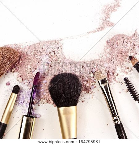 Makeup brushes, lipstick and pencil on a white background, with traces of powder and blush on it. A square template for a makeup artist's business card or flyer design, with copyspace