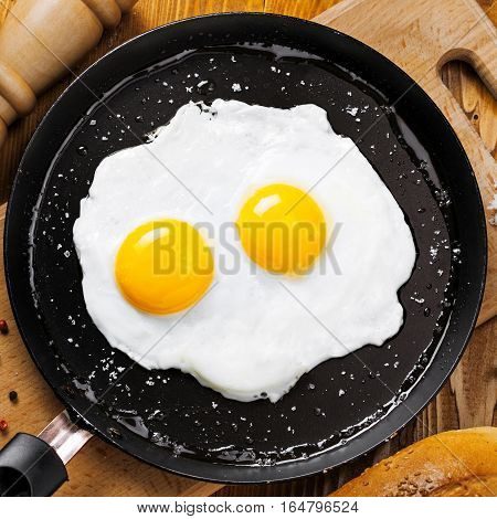 Two fried eggs in a frying pan cooked for breakfast. Delicious international meal on a table. Homemade food top view.