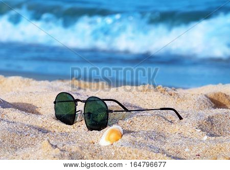 Sun glasses and seashell in the sand on the defocused background of blue sea wave.