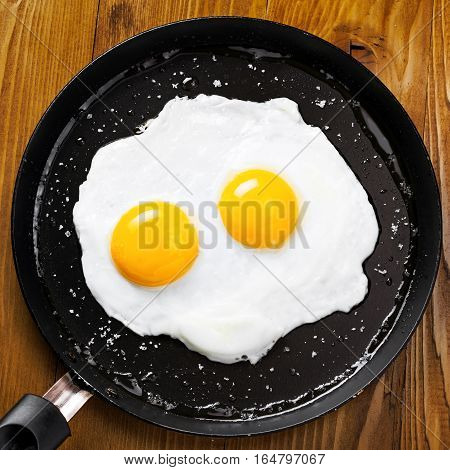 Traditional healthy easy quick breakfast meal made of two fried eggs served on a frying pan. International simple food top view.