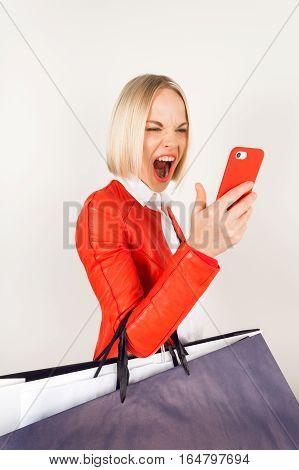 Portrait of young woman in a red jacket with shopping bags on a white background. Woman with shopping bags talking on the phone. Fury