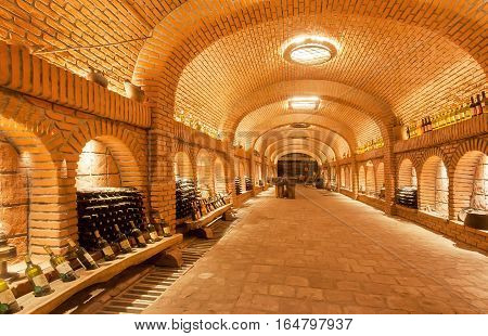 KVARELI, GEORGIA - OCT 3, 2016: Wine bottles waiting for tasting time inside huge cellar Khareba Winery with underground brick tunnel on October 3, 2016. The tunnel was opened in 1962 for the World Wine Congress