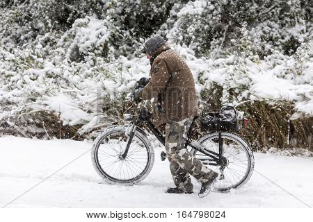Unknown Man Walking With The Bike On A Snowy Landscape In Northern Greece